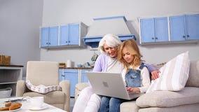 Abuelita y niña que usa el ordenador portátil almacen de video