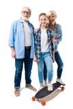 Abuelo, abuela y nieta feliz con el monopatín Imagen de archivo libre de regalías