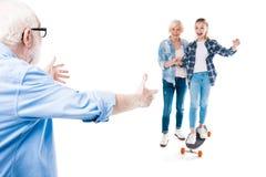 Abuelo, abuela y nieta feliz con el monopatín Fotografía de archivo libre de regalías