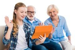 Abuelo, abuela y nieto que usa la tableta digital y sentándose en el sofá fotos de archivo libres de regalías