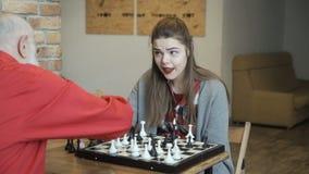 Abuelo con ajedrez del juego de la nieta almacen de video