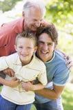 Abuelo con el hijo y el nieto adultos en parque Fotografía de archivo
