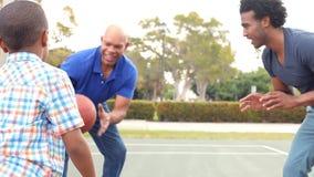 Abuelo con el hijo y el nieto que juegan a baloncesto metrajes