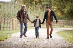 Abuelo con el hijo y el nieto en Autumn Walk In Countryside Together imagen de archivo