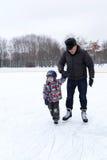 Abuelo con el nieto en la pista de patinaje Fotos de archivo
