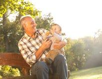 Abuelo con el nieto en parque Foto de archivo