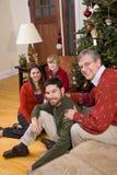 Abuelo con la familia que se sienta por el árbol de navidad fotos de archivo