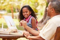 Abuelo con la nieta al aire libre que pinta paisaje Imágenes de archivo libres de regalías