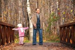 Abuelo con la nieta en el puente de madera Fotografía de archivo