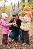 Abuelo con los nietos en bosque en otoño Fotografía de archivo