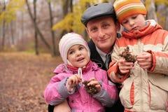 Abuelo con los nietos en bosque en otoño Imagen de archivo libre de regalías