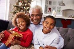 Abuelo con los nietos que abren los regalos de la Navidad Imagen de archivo