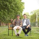 Abuelo con su nieto que se sienta en banco en el parque Imagenes de archivo
