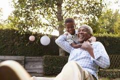 Abuelo de abarcamiento del muchacho negro joven que se sienta en jardín Imagen de archivo