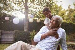 Abuelo de abarcamiento del muchacho negro joven que se sienta en jardín Fotos de archivo libres de regalías