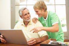 Abuelo de ayuda del nieto adolescente para utilizar la computadora portátil Imágenes de archivo libres de regalías