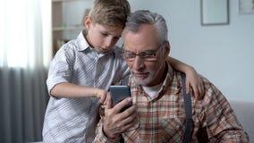 Abuelo de explicación del nieto cómo utilizar el smartphone, uso fácil para los ancianos fotos de archivo
