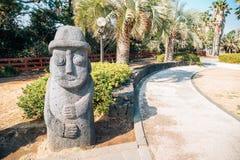Abuelo de piedra del hareubang de Dol con las palmeras tropicales en Daepo Jusangjeolli en la isla de Jeju, Corea fotos de archivo