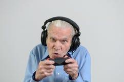 Abuelo divertido que juega a un videojuego en la consola Foto de archivo