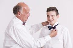 Abuelo elegante que ayuda a su grandon con el cuello Imagen de archivo