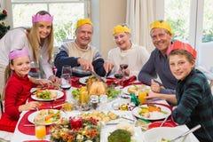 Abuelo en sombrero del partido que talla el pollo durante cena Fotos de archivo libres de regalías