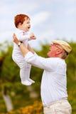 Abuelo feliz que juega con el nieto infantil en jardín de la primavera Fotos de archivo