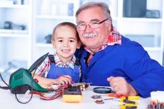 Abuelo feliz y nieto que trabajan junto en taller foto de archivo