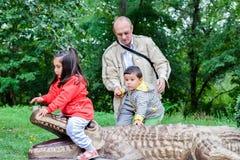 Abuelo feliz y pequeños nietos que juegan en el parque zoológico Fotografía de archivo libre de regalías