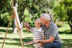 Abuelo feliz y su pintura del nieto Imagen de archivo libre de regalías