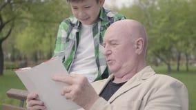 Abuelo lindo y nieto adorable que se sientan en el parque en el banco, viejo hombre del retrato ascendente cercano que lee el lib metrajes