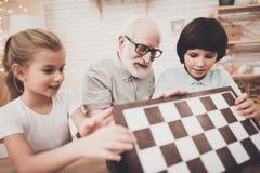 Abuelo, nieto y nieta en casa El abuelo y los niños están abriendo al tablero de ajedrez imagenes de archivo