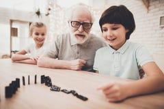 Abuelo, nieto y nieta en casa El abuelo y los niños están jugando con dominós Foto de archivo libre de regalías