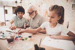 Abuelo, nieto y nieta en casa Los niños están pintando con los cepillos Fotos de archivo libres de regalías