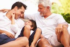 Abuelo, padre And Grandson Sitting al aire libre en casa Fotos de archivo libres de regalías