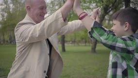 Abuelo positivo y nieto lindo en el alto a cuadros cinco de la camisa en el parque, sonriendo Concepto de las generaciones metrajes