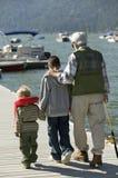 Abuelo que camina con los nietos en el embarcadero Fotos de archivo