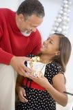 Abuelo que da a su nieta un presente Imágenes de archivo libres de regalías