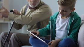 Abuelo que da una conferencia al pequeño muchacho que juega al juego de la tableta, comportamiento critizing del niño almacen de metraje de vídeo