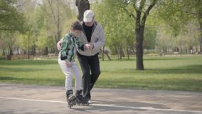 Abuelo que ense?a a su nieto a montar pcteres de ruedas en el parque La mano de la tenencia del viejo hombre del muchacho y de ay metrajes
