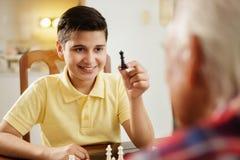 Abuelo que juega al juego de mesa del ajedrez con el nieto en casa Foto de archivo libre de regalías