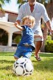 Abuelo que juega a fútbol con el nieto en jardín fotografía de archivo libre de regalías