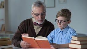 Abuelo que lee en voz alta historia de aventura al pequeño nieto, al cuidado de la familia y al calor almacen de video