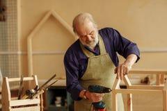 Abuelo que trabaja en casa del pájaro en el taller Imágenes de archivo libres de regalías