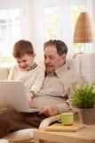 Abuelo que usa el ordenador en el país Imágenes de archivo libres de regalías