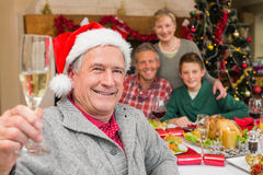Abuelo sonriente en el sombrero de santa que tuesta con champán Imagen de archivo libre de regalías