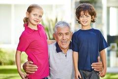Abuelo y dos nietos en jardín Imágenes de archivo libres de regalías