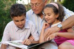Abuelo y libro de lectura de los cabritos Imagenes de archivo