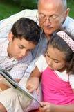 Abuelo y libro de lectura de los cabritos Fotografía de archivo