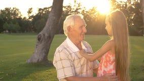 Abuelo y niña que hablan al aire libre metrajes