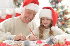 Abuelo y niño en los sombreros de Papá Noel Foto de archivo libre de regalías